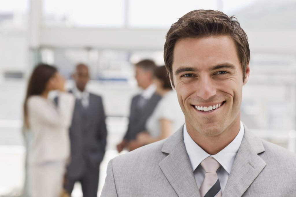 Portrait of happy young businessman with colleagues in the background