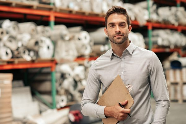 Portrait of a manager holding a clipboard while standing on a carpet warehouse floor with inventory on shelves in the background